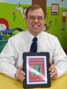 "Here I am with the second ""Noah and Logan"" book at the Pulaski Public Library for their Disability Awareness Day.  The mural on the background wall is much larger than this photo may make it seem, and it is indeed very vibrant and colorful!"