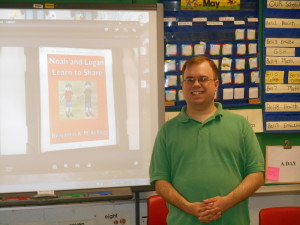 "I stand next to my first ""Noah and Logan"" book at Fulton High School, May 2015.  The classroom has a projector, very handy for showing my book to the entire class."